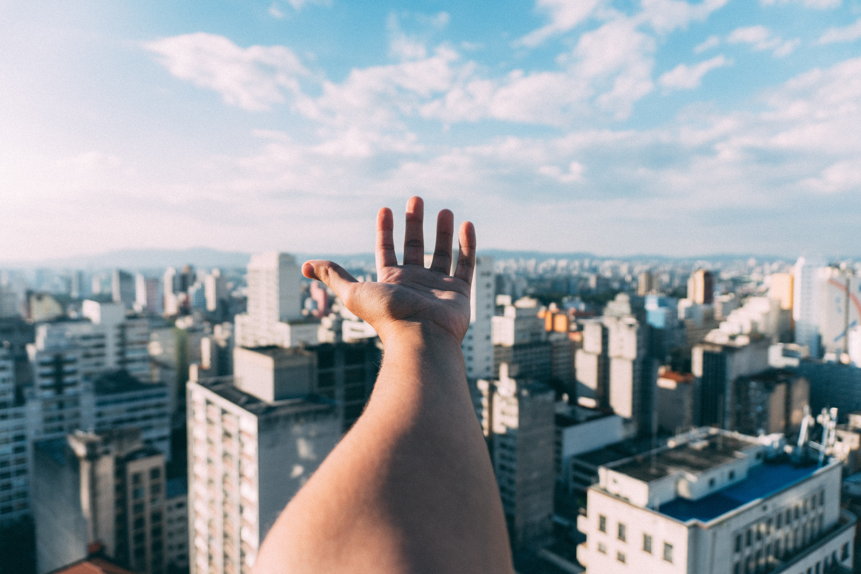 ciudades sostenibles, imagen de una mano por encima de una ciudad con cielo despejado